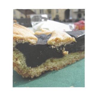Stück des Schokoladenkuchens auf Grünbuchserviette Notizblock