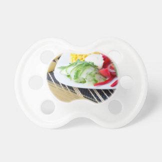 Stücke frisches rohes Gemüse auf einer weißen Schnuller