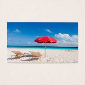 Stühle und Regenschirme auf einem tropischen Visitenkarte