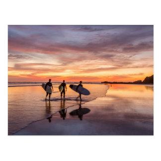 Surfer am Sonnenuntergang gehend auf Strand, Costa Postkarte