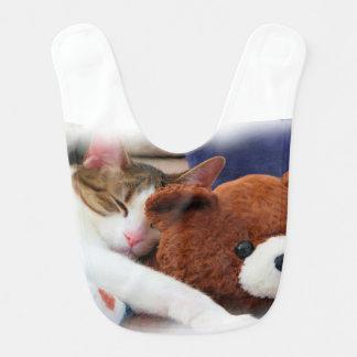 Süße schläfrige Miezekatze mit Teddybären Lätzchen