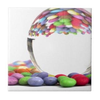 Süßigkeiten, die in einem Glasball sich Kleine Quadratische Fliese