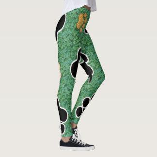 TAN und schwarze Tatze drucken auf grünem Gras Leggings