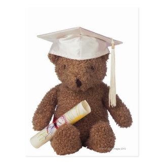 Teddybär tragender Mortarboard und mit Postkarte