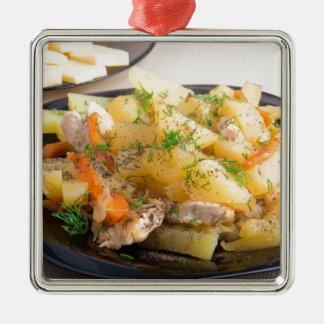 Teller der gedämpften Kartoffeln mit Fleisch und Quadratisches Silberfarbenes Ornament
