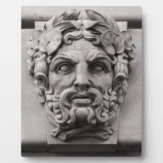 Terrakotta-Steingesichter auf historischem Gebäude Fotoplatte
