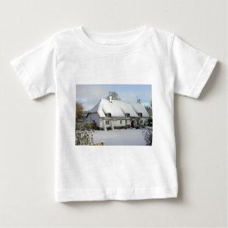 Thatched englische Hütte im Schnee Baby T-shirt