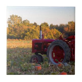 Traktor auf einem Kürbisgebiet Keramikfliese
