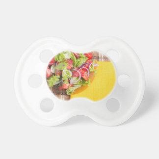 Transparente Platte mit frischem Sommersalat auf Schnuller