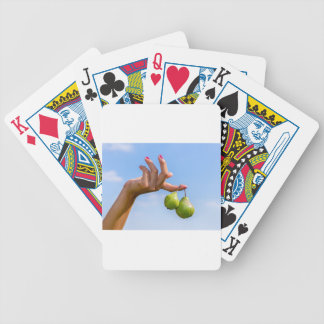 Übergeben Sie das Halten von zwei hängenden grünen Bicycle Spielkarten