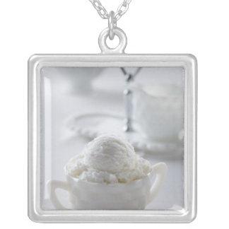 Vanilleeiscreme in einer weißen Umwelt Versilberte Kette