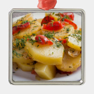 Vegetarischer Teller der gedämpften Kartoffeln und Quadratisches Silberfarbenes Ornament
