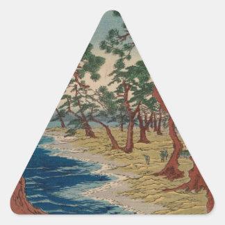 Verdrehte Bäume durch das Ufer Dreieckiger Aufkleber