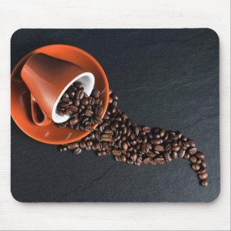 Verschüttete Kaffeebohnen und Tasse Mauspad