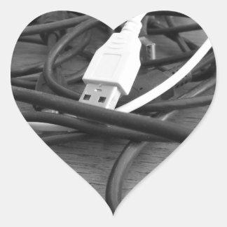 Verwicklung der staubigen Computerkabel mit Herz-Aufkleber