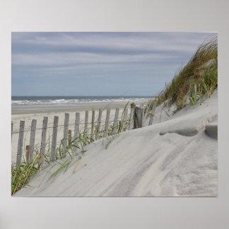 Verwitterter Zaun und Sanddünen am Strand Poster