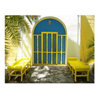 Verzierte blaue Tür mit gelben Bänke Postkarte