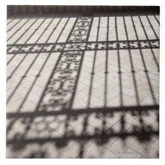 verziertes Eisen, das Schatten auf Fliesenboden Fliese