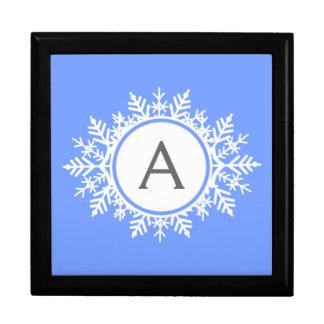 Verziertes weißes Schneeflocke-Monogramm auf Geschenkbox