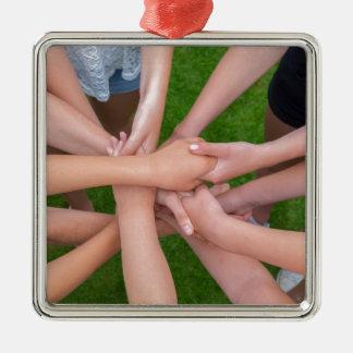 Viele Arme der Kinder, die Hände zusammenhalten Quadratisches Silberfarbenes Ornament