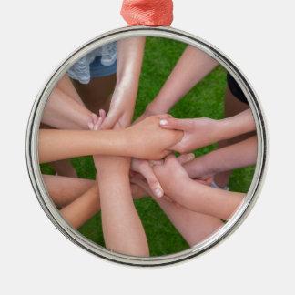 Viele Arme der Kinder, die Hände zusammenhalten Rundes Silberfarbenes Ornament