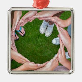 Viele Arme der Kinder mit den Händen, die Kreis Quadratisches Silberfarbenes Ornament