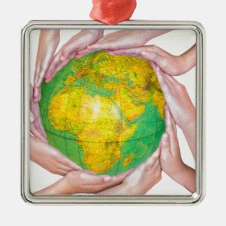 Viele Arme der Kinder mit den Händen, die Kugel Quadratisches Silberfarbenes Ornament