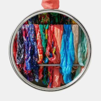 Viele bunten Schals, die am Markt hängen Rundes Silberfarbenes Ornament
