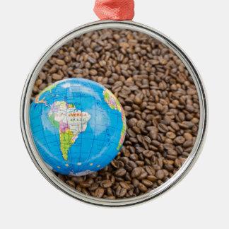 Viele ganzen Kaffeebohnen mit Südamerika-Kugel Rundes Silberfarbenes Ornament