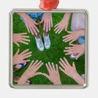 Viele Kinder übergibt das Anschließen Kreis über Quadratisches Silberfarbenes Ornament