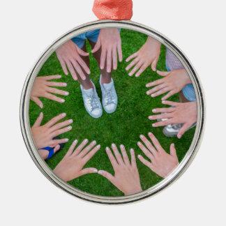 Viele Kinder übergibt das Anschließen Kreis über Silbernes Ornament