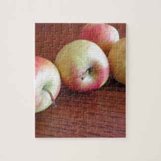 Vier reife Äpfel auf hölzerner Tabelle Puzzle