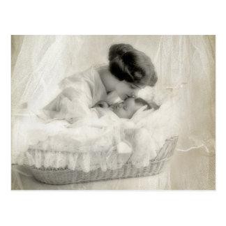 Vintage Mutter, die Baby in der Korbwiege küsst Postkarte