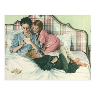 Vintage Mutter-Lesekarten im Bett mit den Kindern