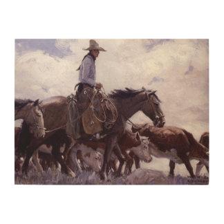 Vintager Cowboy mit seiner Herde des Viehs durch Holzdruck