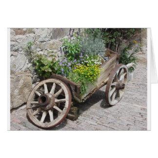 Vintager Gartenkarren mit wilden Blumen und Karte
