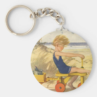 Vintager Junge, der am Strand mit Sand-Spielwaren Schlüsselanhänger