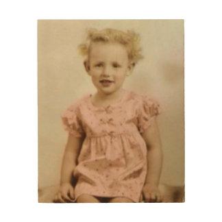 Vintages kleines blondes Mädchen in der rosa Holzleinwand