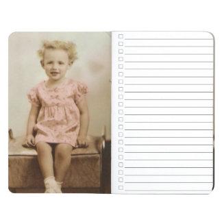 Vintages kleines Mädchen in der rosa Taschennotizbuch