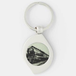 Vintages Zug-Foto in der Bewegung mit Unschärfe Silberfarbener Wirbel Schlüsselanhänger