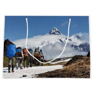 Wanderer, die auf Berg auf Hintergrundvulkanen Große Geschenktüte