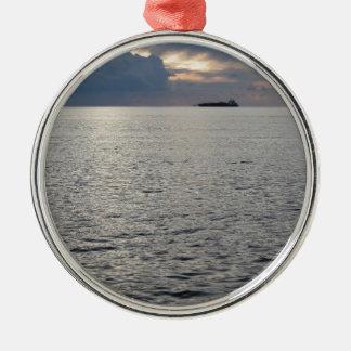 Warmer Seesonnenuntergang mit Frachtschiff am Silbernes Ornament