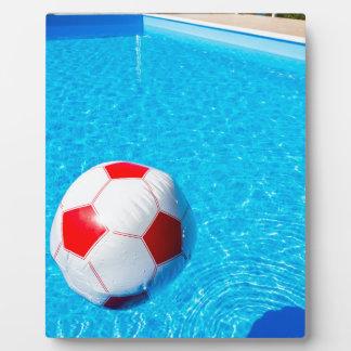 Wasserball, der auf Wasser im Swimmingpool Fotoplatte