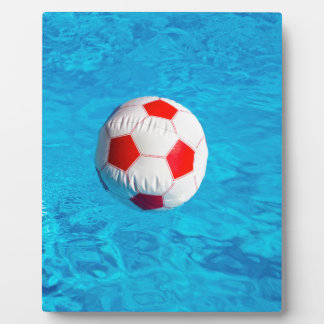 Wasserball, der in blauen Swimmingpool schwimmt Fotoplatte