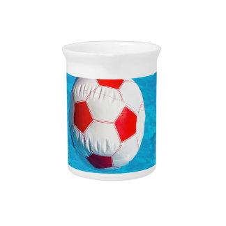Wasserball, der in blauen Swimmingpool schwimmt Getränke Pitcher