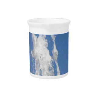 Wässern Sie das Sprühen von einem Brunnen gegen Getränke Pitcher