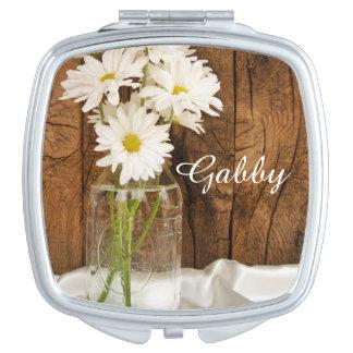 Weckglas und weiße Gänseblümchen, die Wedding sind Taschenspiegel