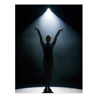 Weiblicher Gymnast darstellend im Scheinwerfer, Postkarte