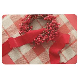 Weihnachtsbeeren und -Wreath auf kariertem Bodenmatte