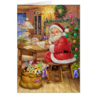 Weihnachtsmann, der an seinem Schreibtisch Karte
